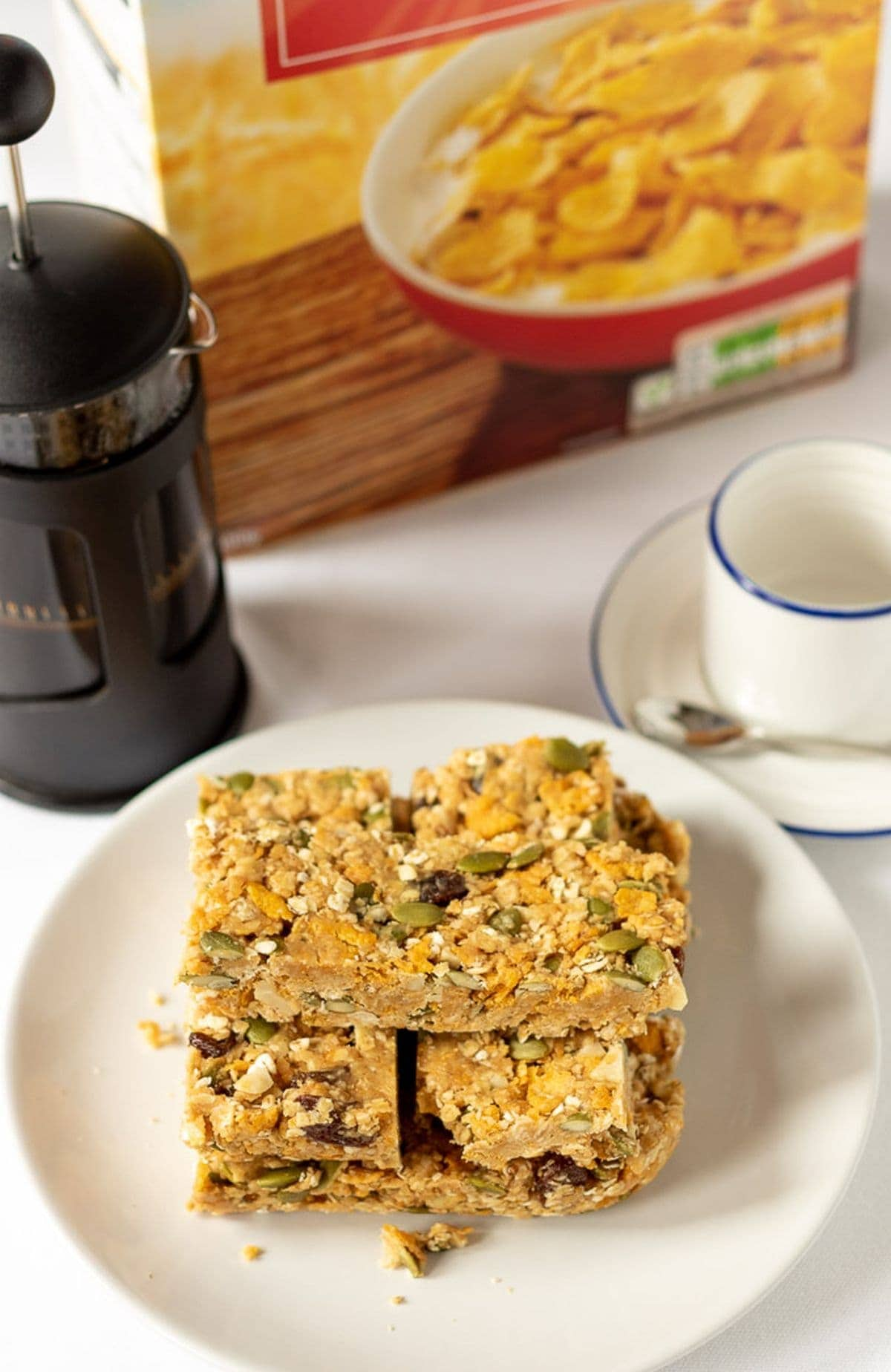 No-bake cereal breakfast bars stacked on a plate with a cafetiere, coffee cup and a box of cereal in the background.