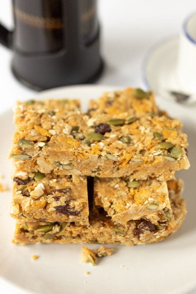 No-bake cereal breakfast bars stacked on a plate with a cafetiere in the background.
