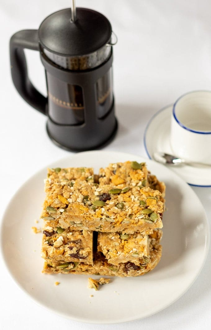 Birds eye view of a stack of no-bake cereal breakfast bars on a plate with the coffee cup and cafetiere in the background.