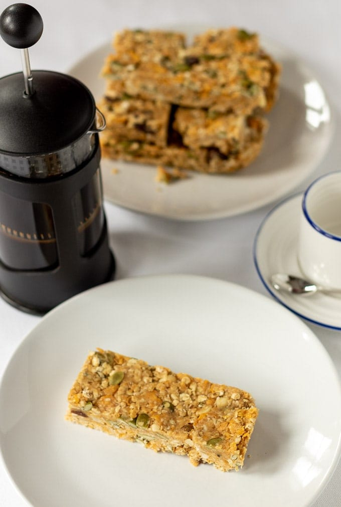 A no-bake cereal breakfast bar on a plate with a cafetiere, coffee cup and stack of cereal bars in the background.