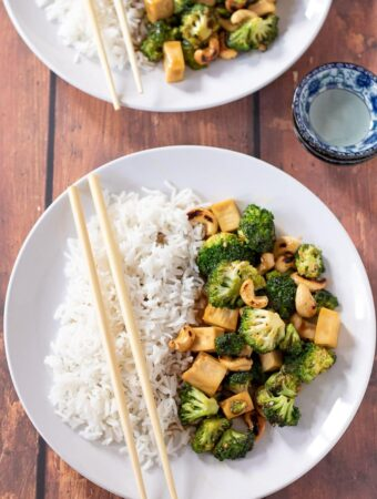 Birds eye view of two plates of sticky peanut butter tofu stir-fry served with rice and chop sticks placed over plates.