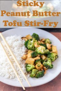 A plate of sticky peanut butter tofu stir-fry served with rice and chop sticks placed over. Pin title text overlay at top.