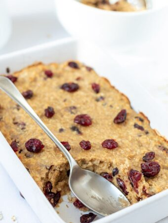 Baked cranberry oatmeal in a baking dish with a serving taken out and a serving spoon in the dish.