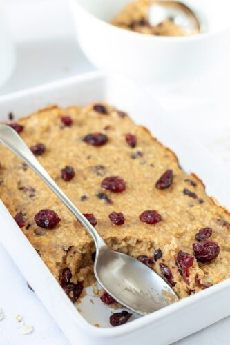Baked cranberry oatmeal in a baking dish with a serving taken out and a serving spoon.