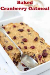 Baked cranberry oatmeal in casserole dish with a serving taking out of it and a spoon in its place.
