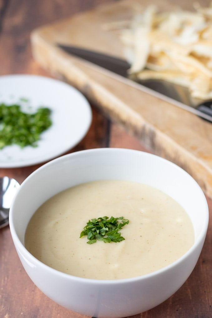 A bowl of parsnip soup with a saucer of parsley garnish in the background.