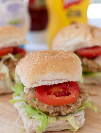 Three leftover chicken burgers in buns with iceberg lettuce and sliced tomatoes. All sitting on a bread board with condiments in the background.