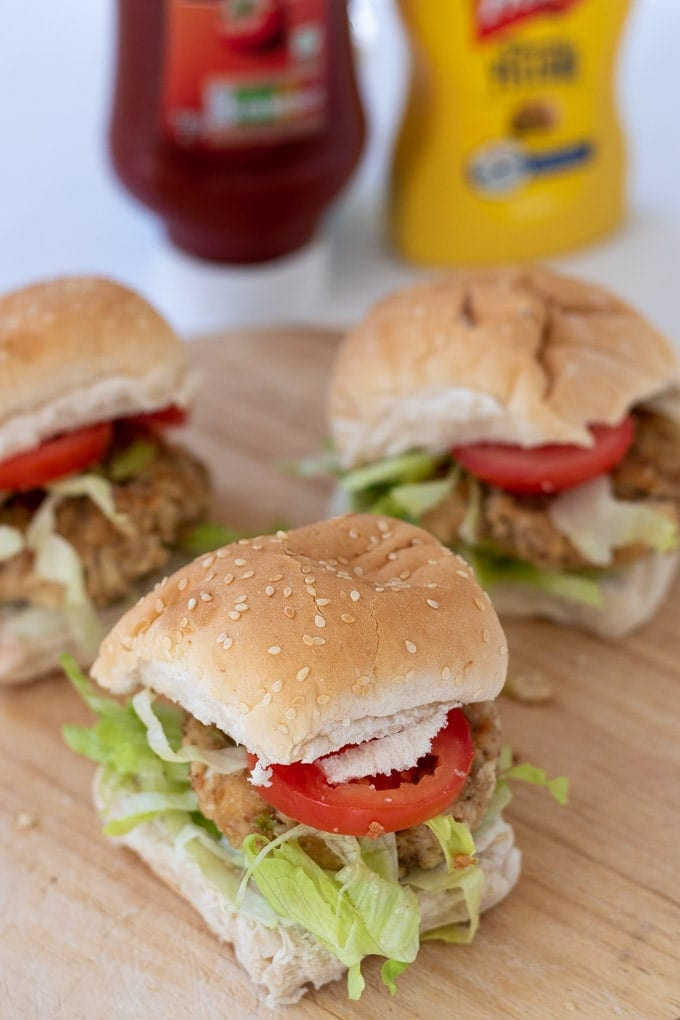 A chopping board with three leftover chicken burgers on served in buns with iceberg lettuce and sliced tomatoes.