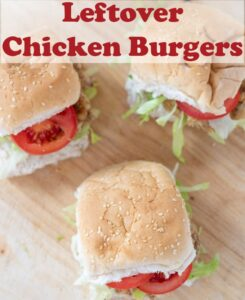 Three leftover chicken burgers in buns with iceberg lettuce and sliced tomatoes. All sitting on a bread board. Pin title text overlay at top.