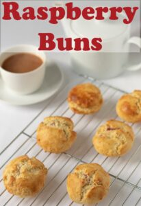 A wire rack of six raspberry buns with a cup of tea and teapot in the background. Pin title text overlay at top.