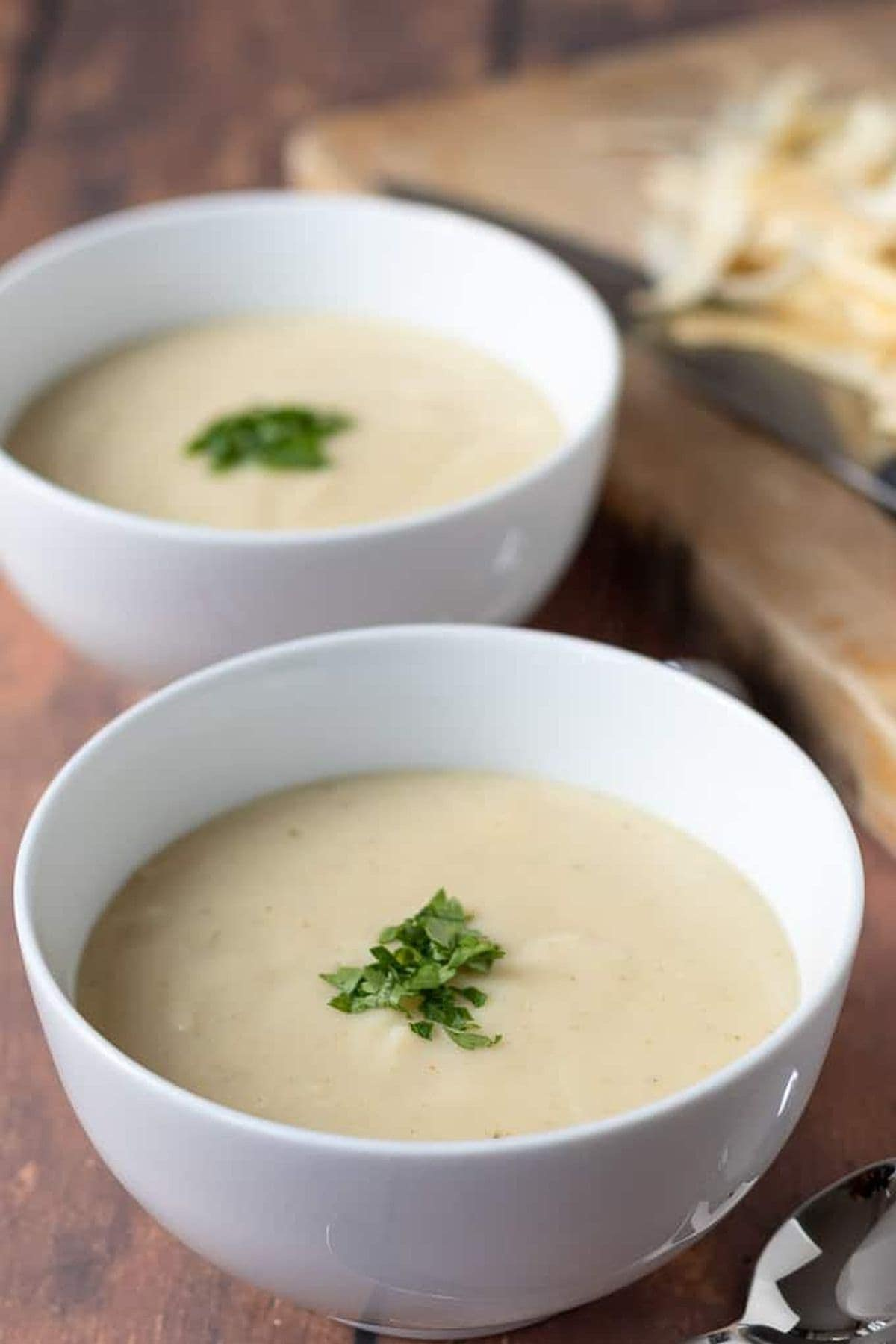 Two bowls of creamy parsnip soup, one in front of the other with a chopping board in the background.