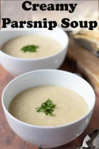 Two bowls of creamy parsnip soup one in front of the other garnished with parsley and chopping board with parsnip peelings on in the background.