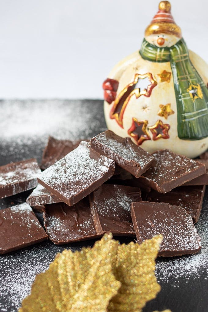 Squares of easy healthy peppermint fudge arranged on a slate dusted with icing sugar with a porcelain snowman in the background and a gold leaf decoration in the front.