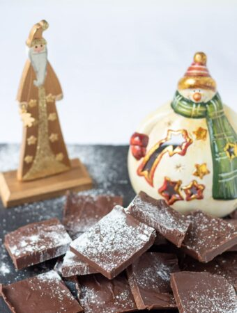 Easy healthy peppermint fudge squares on a slate dusted with icing sugar and a santa and snowman Christmas decoration in the background.