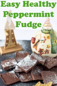 Squares fof easy healthy peppermint fudge on a slate with a festive snowman Christmas decoaration and a wizard in the background.
