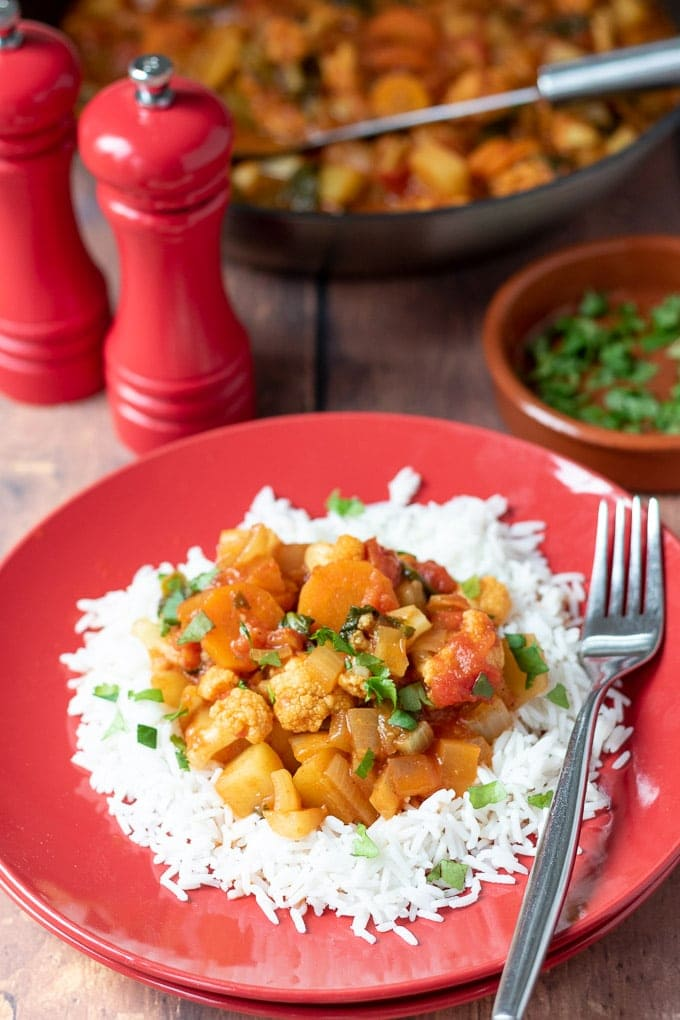 A plate of easy mixed vegetable curry served on a bed of basmati rice with salt and pepper cellars, a dish of chopped coriander and a pan in the background.