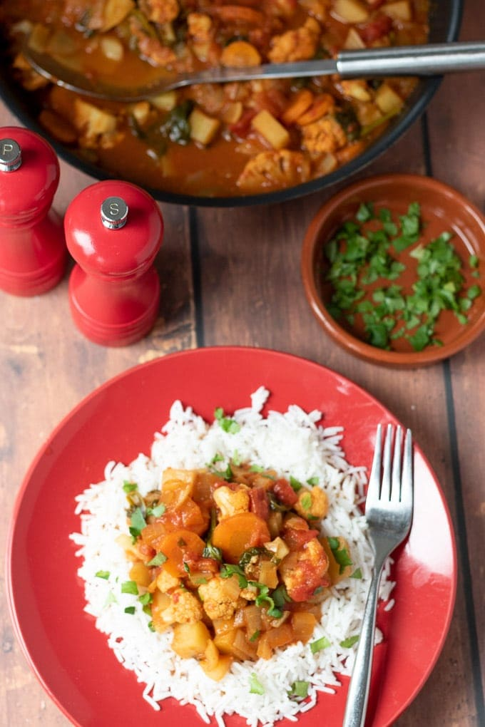 Birds eye view of a plate of easy mixed vegetable curry on a bed of basmati rice with a pan of cooked curry, salt and pepper cellars and a dish of chopped coriander at the top.