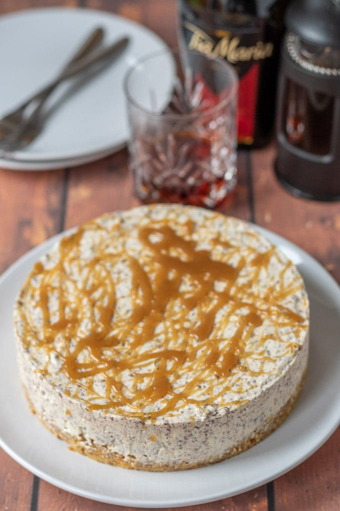 Full uncut no-bake Tia Maria cheesecake with a glass of Tia Maria, plates and bottle in the background.