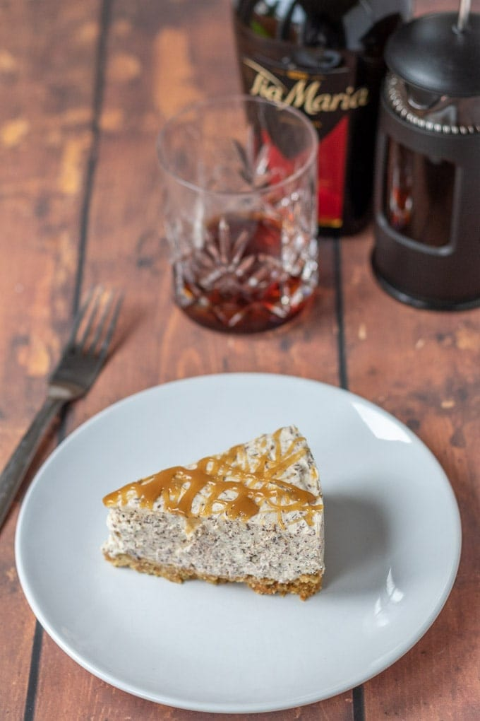 A slice of no-bake Tia Maria cheesecake on a plate with a fork beside it and bottle, glass and cafatiere in the background.