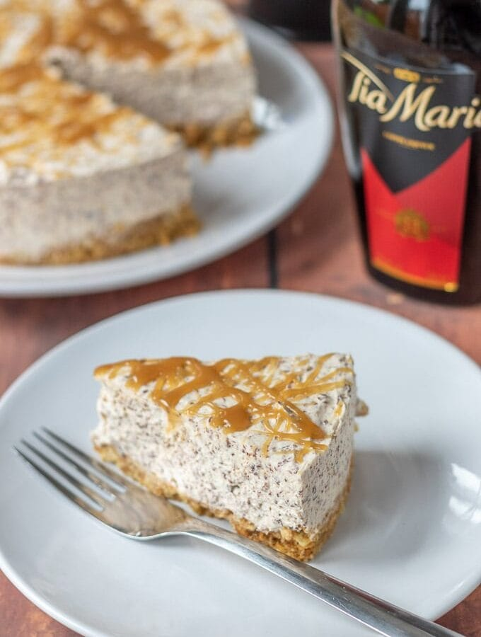 A slice of no-bake Tia Maria cheesecake on a plate with the full cake and a bottle of Tia Maria in the background.