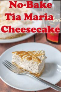 A slice of Tia Maria cheesecake on a plate with a bottle of Tia Maria and the rest of the cheesecake in the background.