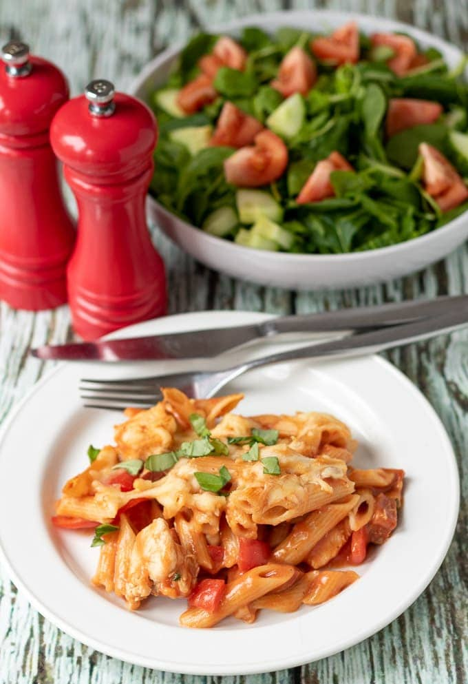 A portion of chicken and chorizo pasta bake served on a plate with a knife and fork on, salt and pepper cellar and bowl of side salad at the back.