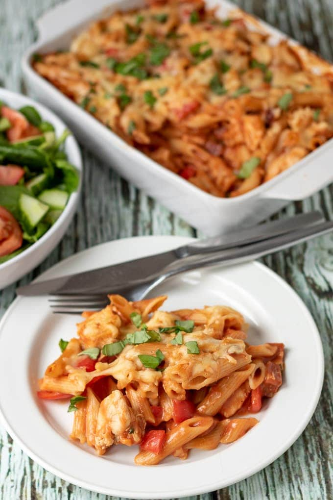 Chicken and chorizo pasta bake served on a plate with a side salad to the left and the remainder bake in the background.