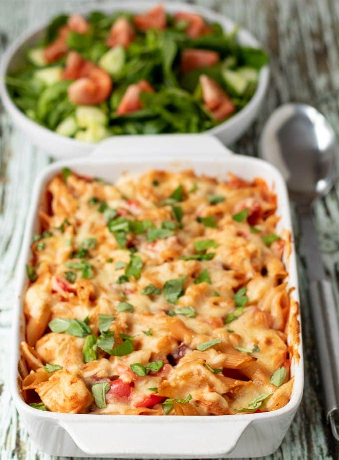 Chicken and chorizo pasta bake with a serving spoon to the right and a bowl of side salad in the background.