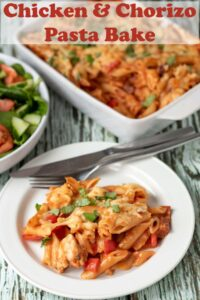 Chicken and Chorizo pasta bake served on a plate. A bowl of salad above and the rest of the bake in a casserole dish beside. Pin title text overlay at top.
