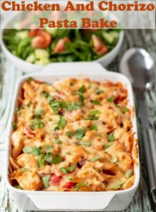 Chicken and Chorizo Pasta Bake ready to serve with a side salad in the background.