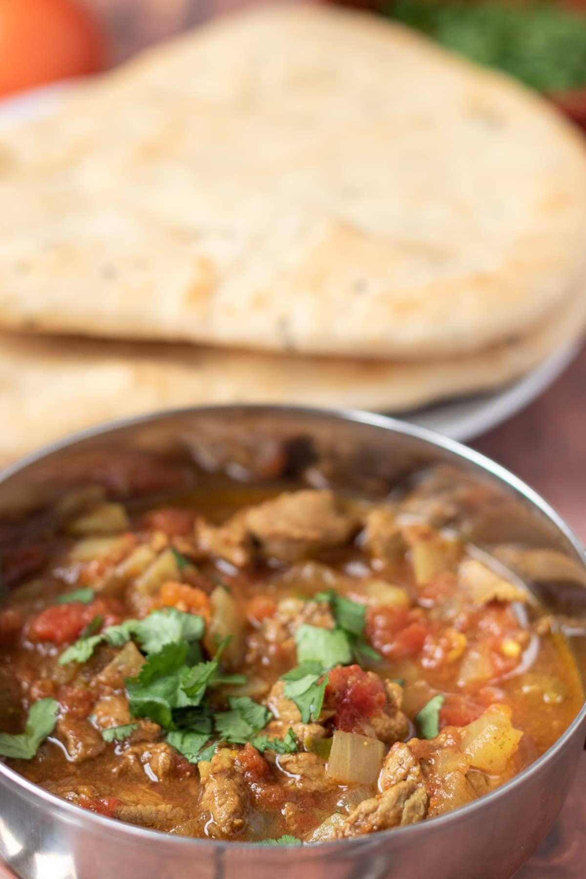 Close up of a balti dish of slow cooker lamb curry with naan breads in the background.