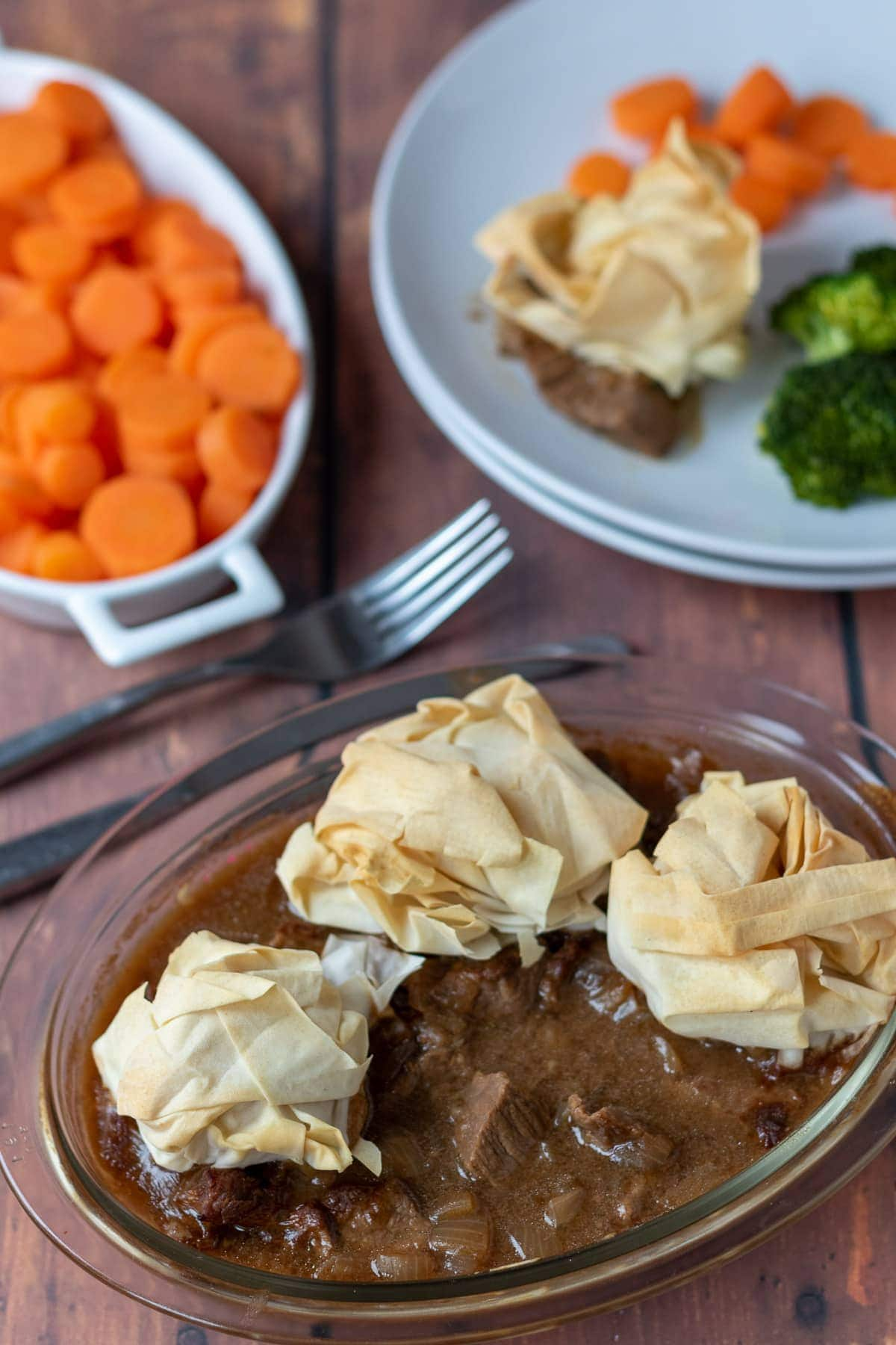 Steak pie with filo pastry topping birds eye view. Plate in the background has a portion of steak pie with filo pastry topping on it and sides of carrots and broccoli.