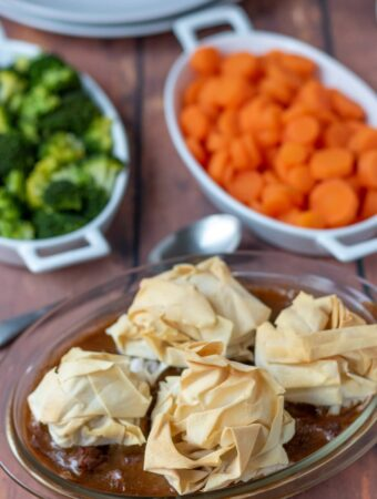 Steak pie with filo pastry topping and sides of broccoli and carrots in serving dishes in the background.