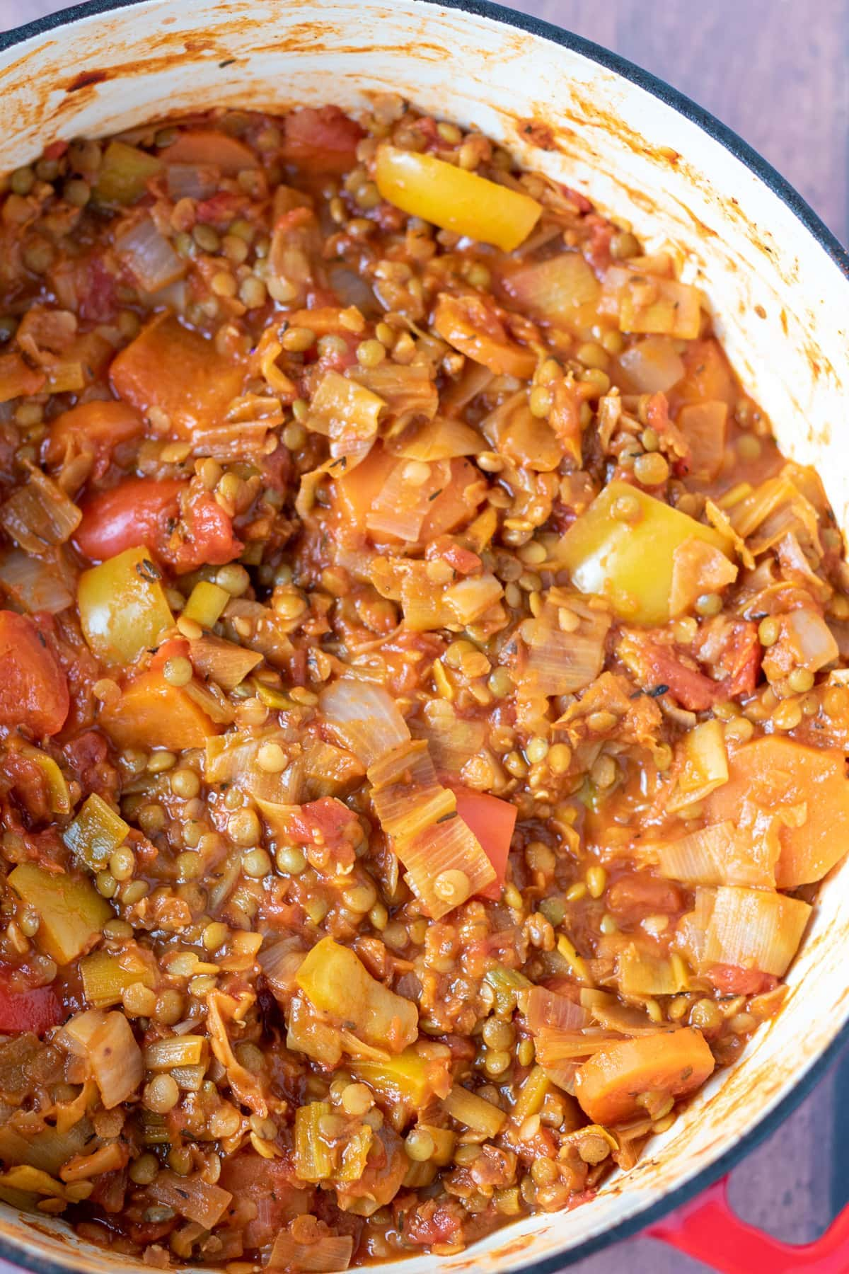 Birds eye view of a large casserole pot of cooked winter vegetable stew.