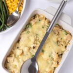 Birds eye view of a cooked casserole dish of honey mustard chicken pasta bake with a serving spoon on top. With green beans and sweetcorn in a side dish.