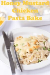 A portion of honey mustard chicken pasta bake served on a plate with a knife and fork to the left hand side. Pin title text overlay at top.