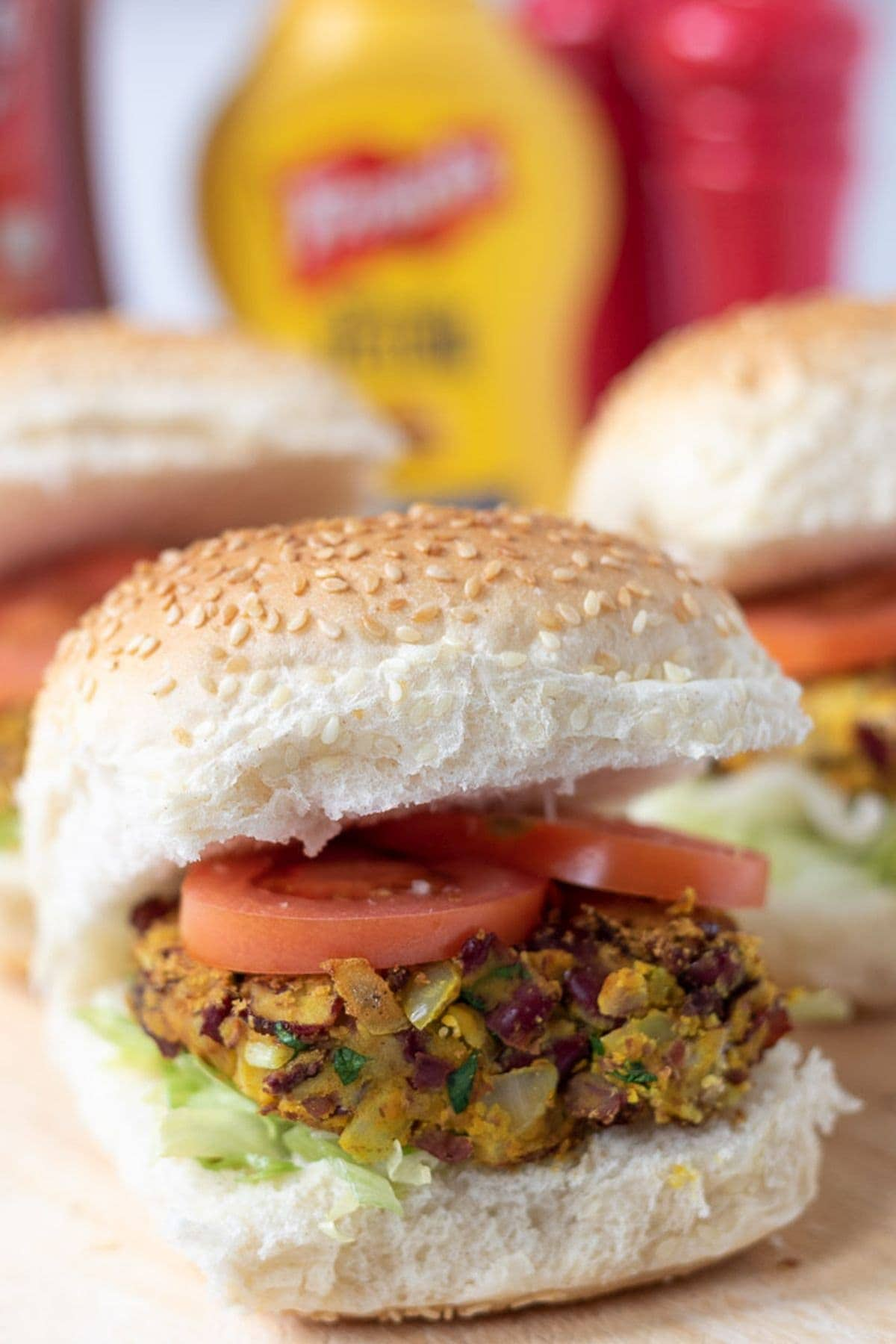 Close up of a kidney bean burger in a burger roll. A selection of bottles relishes in the background.