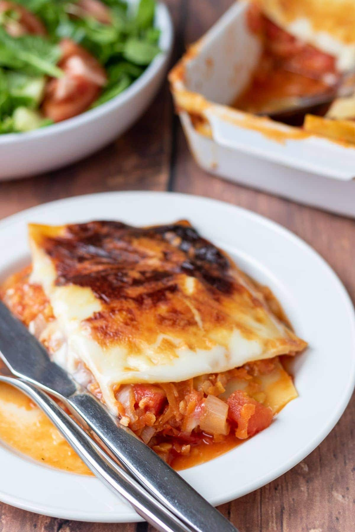 A portion of lentil lasagne placed on a plate with a knife and fork. Side salad and casserole dish in the background.