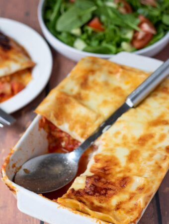 Red lentil lasagne with a portion taken out of one corner. A spoon in its place and a side salad in the background.