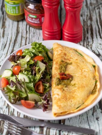 A plated spinach pesto and sundried tomato omelette with a side salad. Salt and pepper cellars and a jar of pesto and a jar of sundried tomatoes in the background.