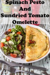 A plate of spinach pesto and sundried omelette with salad at the side.