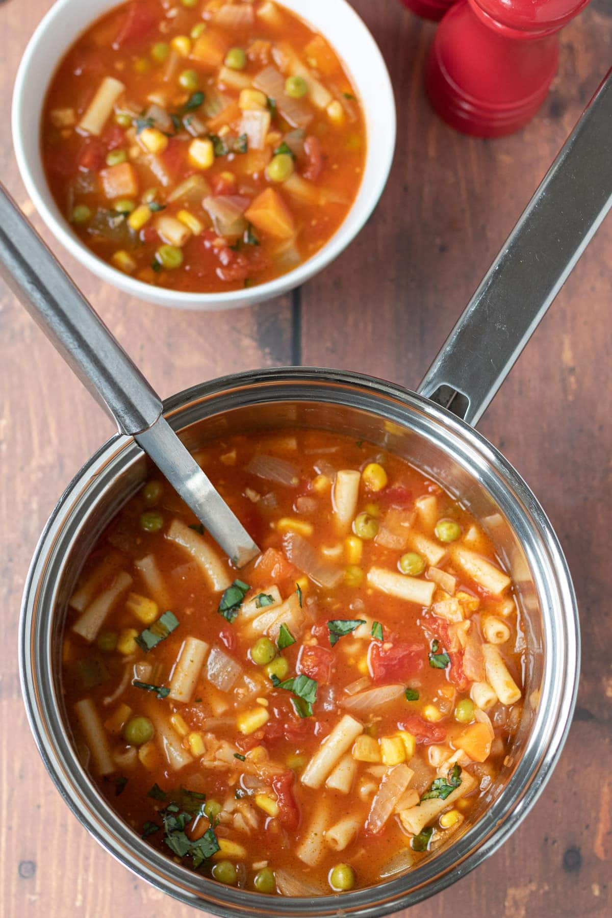 Birds eye view of a pot of pasta vegetable soup with a serving spoon in. A bowl of served soup at the top.