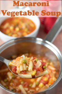 A spoonful of Macaroni soup being lifted from the pot. Served soup in a bowl in the background. Pin title text overlay at top.