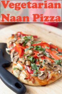 Vegetarian naan pizza on a chopping board with a pizza cutter beside it. Pin title text overlay at top.