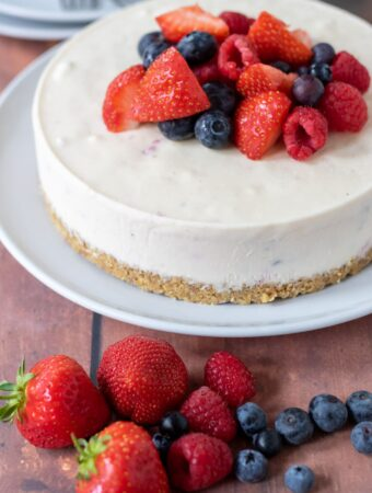 Summer fruits cheesecake in the background with a mixture of strawberries, raspberries and blueberries at the front.