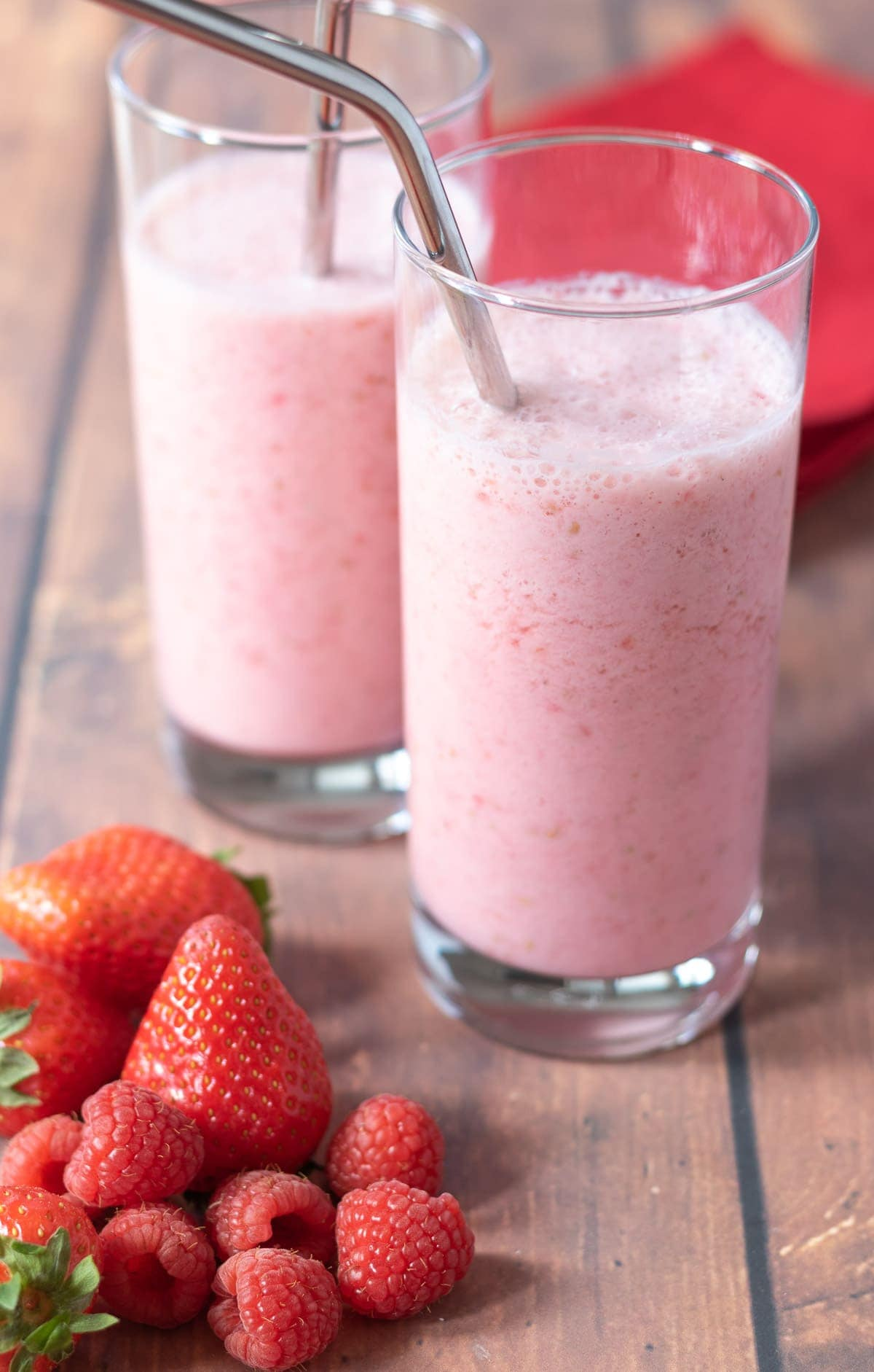 Two glasses of strawberry raspberry smoothie with silver drinking straws in. A pile of strawberries and raspberries at the front and a red serviette in the background.