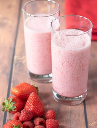 Two tall glasses of strawberry and raspberry smoothie in the center with a pile of strawberries and raspberries in front of the glasses. Serviette to the rear.