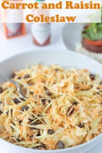 A large salad dish of carrot and raisin coleslaw with a serving spoon in. Pin title text overlay at top.