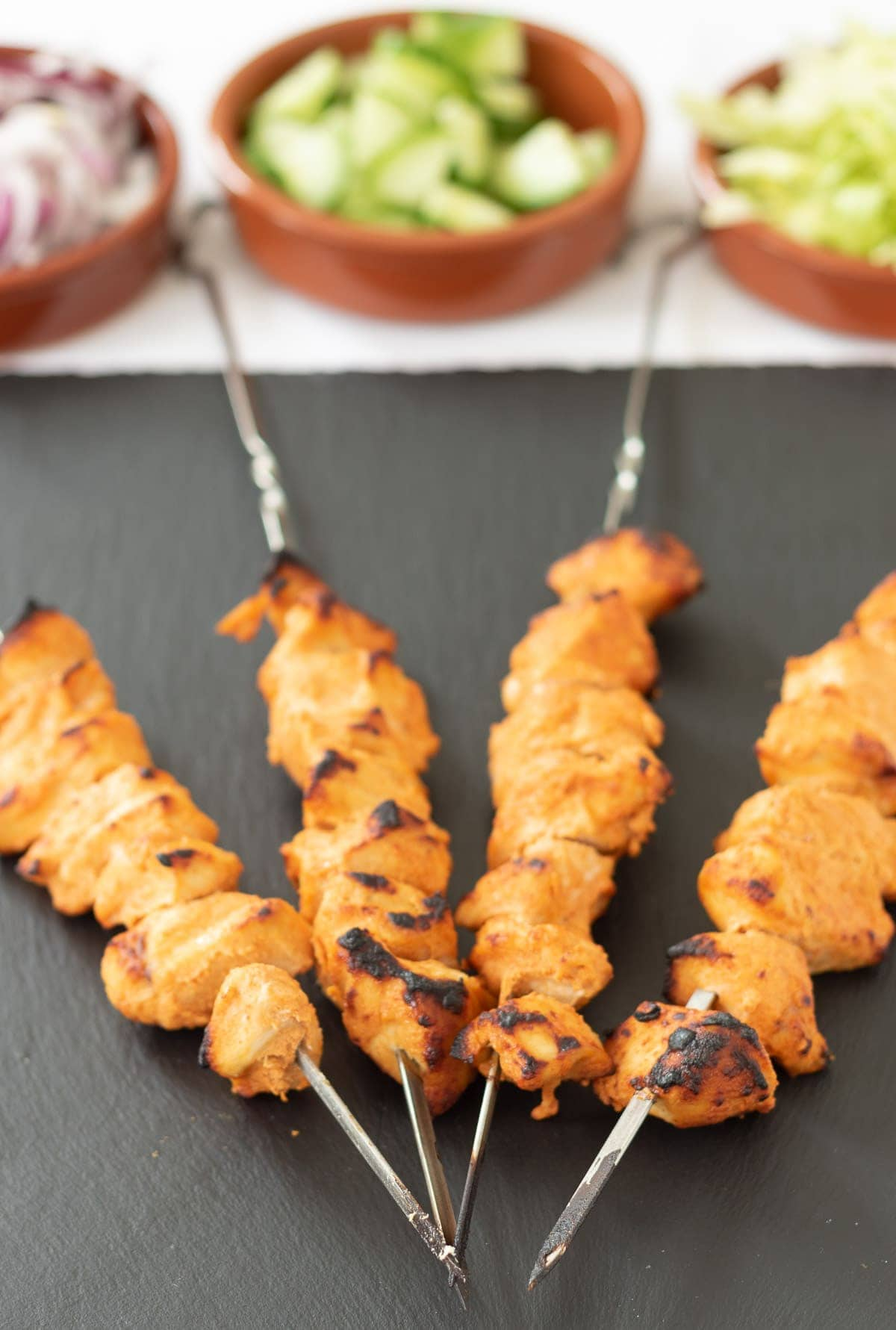 Four grilled cooked chicken tikka skewers.