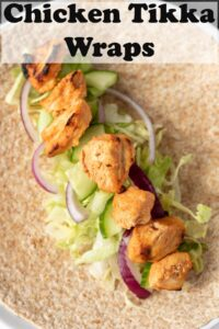 An unrolled chicken tikka wrap. Chicken placed on iceberg lettuce with sliced red onion and cucumber. Pin title text overlay at top.